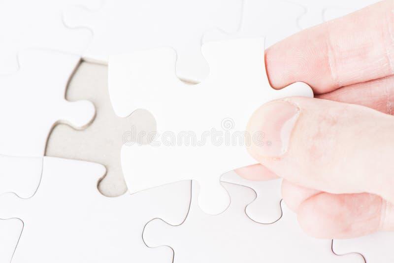 Hand die het laatste raadselstuk plaatsen stock afbeelding