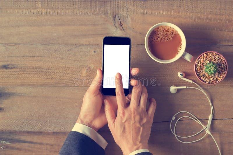 Hand die het telefoon witte scherm op houten achtergrond met behulp van stock afbeeldingen