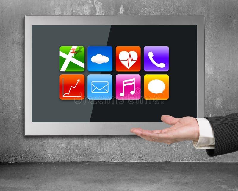 Hand die het zwarte brede vlakke TV-scherm met app pictogrammen tonen stock afbeelding