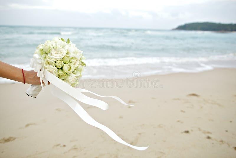 Hand, die Hochzeitsblumenstrauß mit Strandhintergrund hält lizenzfreie stockbilder
