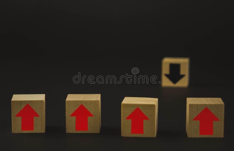 Hand die houten kubusblok op hoogste piramide houten blokken zetten met rode pijlen die tegengesteld aan de zwarte pijlen onder o stock foto