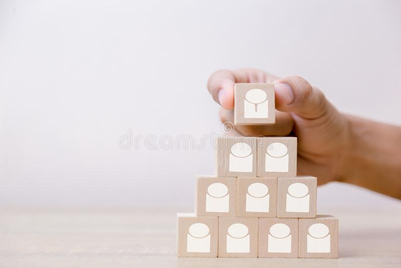 Hand die houten kubusblok op hoogste piramide, menselijk middelbeheer en rekruterings bedrijfsconcept, Bedrijfsstrategie zetten a stock fotografie