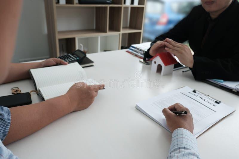 Hand die huismodel beschermen cliënt die huisverzekering ondertekenen contr stock foto