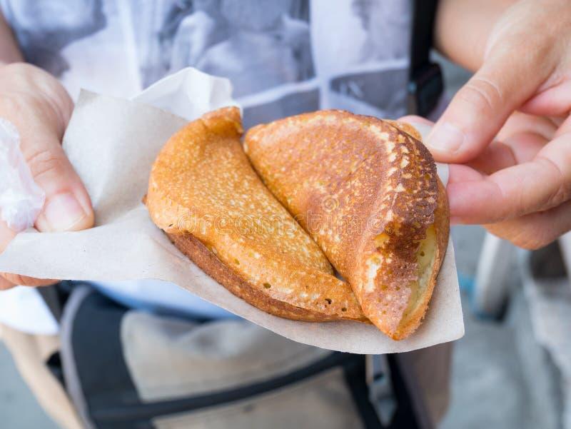 Hand die Indonesisch straatvoedsel, zoete martabak, traditionele pannekoek dicht tegenhouden royalty-vrije stock foto