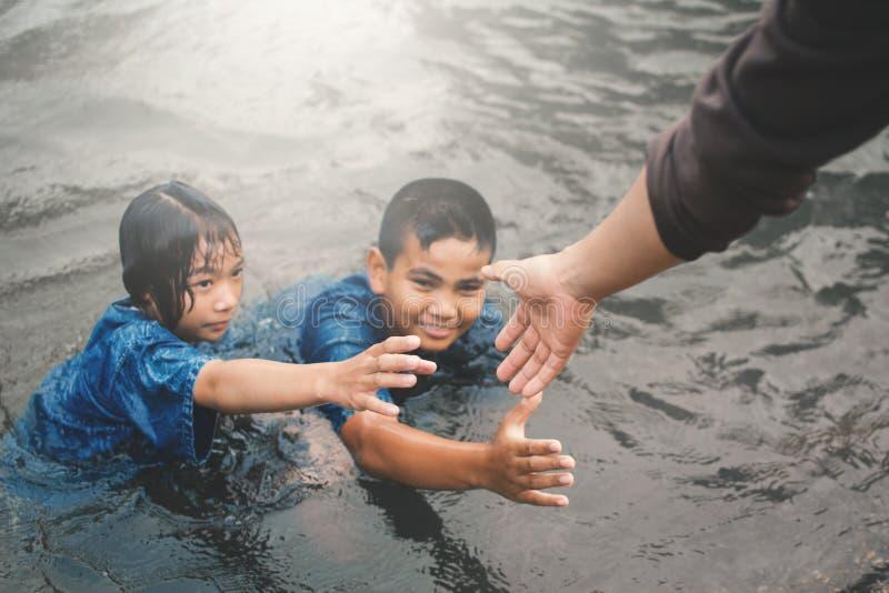 hand die kinderen in de pool helpen royalty-vrije stock foto