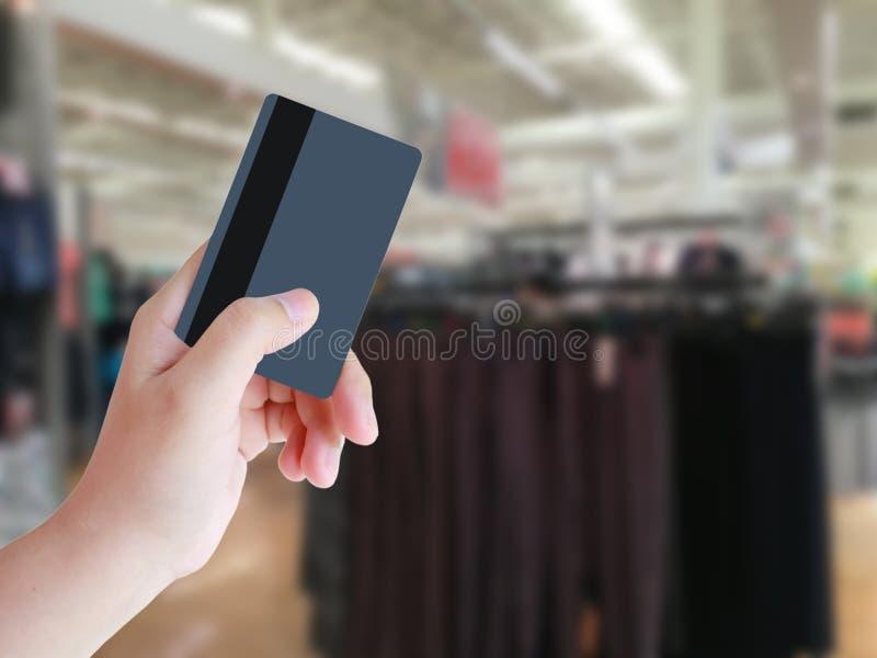 Hand, die Kreditkarte mit Bekleidungsgeschäft hält lizenzfreie stockfotografie