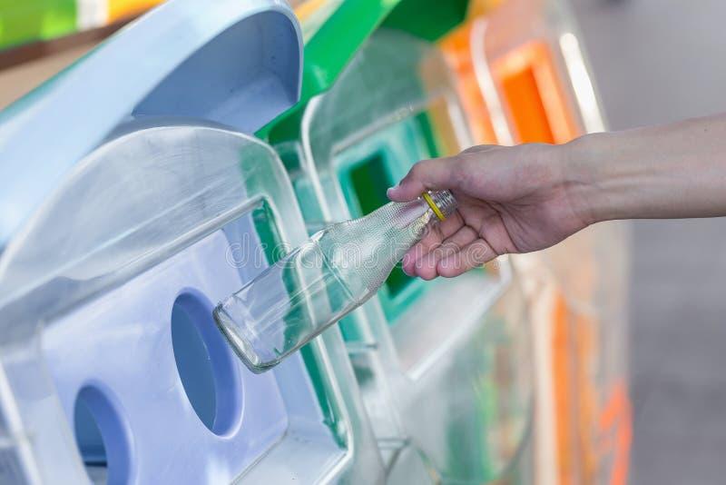 Hand die lege glasfles werpen in het afval royalty-vrije stock afbeeldingen
