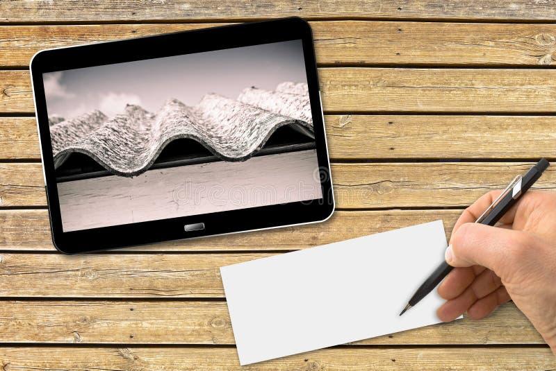 Hand die met een potlood op een leeg blad boven een houten lijst met een digitale tablet schrijven die een gevaarlijk asbestdak t royalty-vrije stock foto's