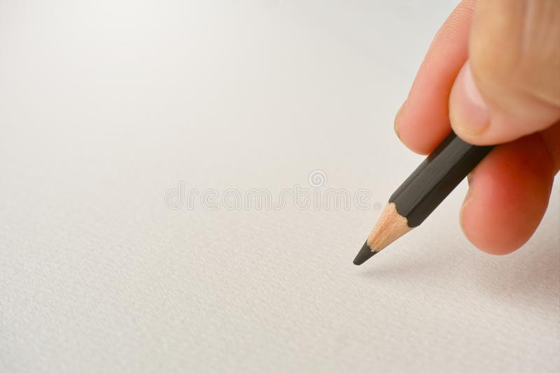 Hand die met potlood op witte schetsdocument achtergrond met vrije ruimte voor het tonen van bericht of het schetsen van ontwerp  stock afbeeldingen