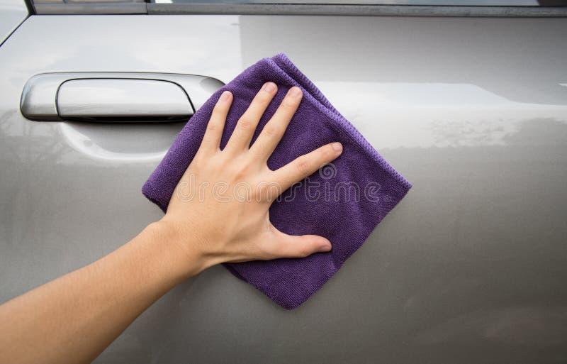 Hand, die microfiber Stoff poliert graues Auto hält lizenzfreie stockbilder