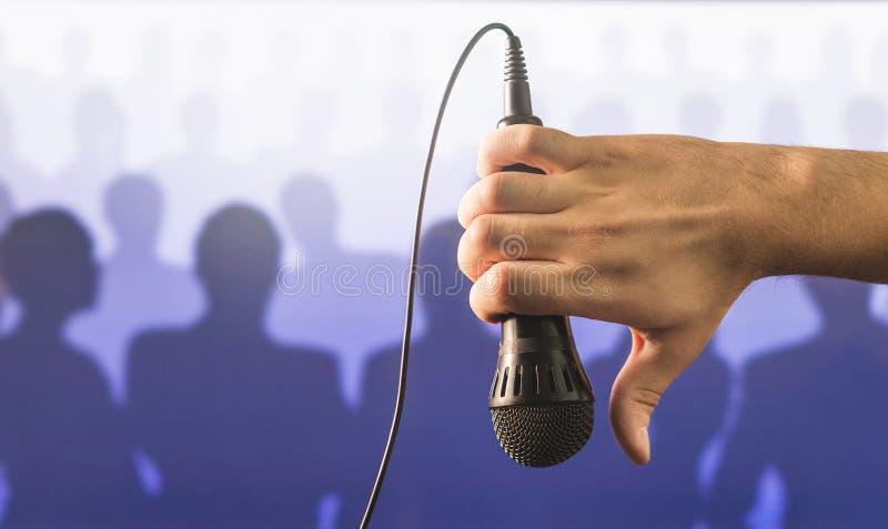 Hand, die Mikrofon hält und unten Daumen zeigt lizenzfreies stockfoto