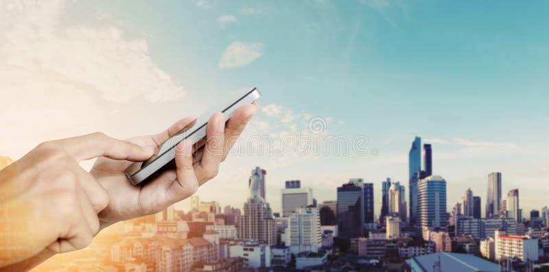 Hand die mobiele slimme telefoon, de achtergrond van de de stadszonsopgang van Bangkok met behulp van royalty-vrije stock afbeeldingen
