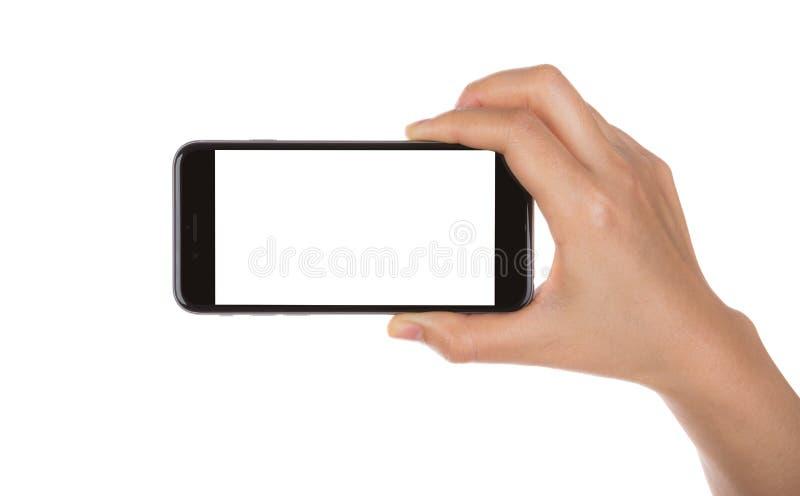 Hand die mobiele slimme telefoon met het lege die scherm houden op wh wordt geïsoleerd stock afbeeldingen