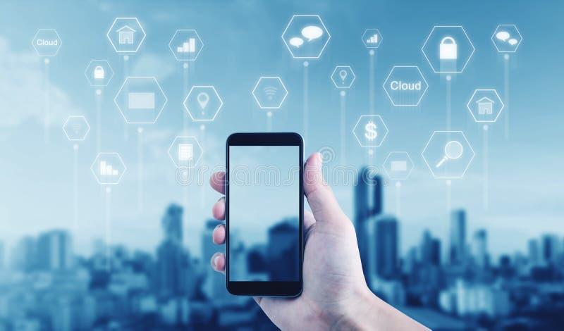 Hand die mobiele slimme telefoon met toepassingspictogrammen houden, stadsachtergrond royalty-vrije stock foto's