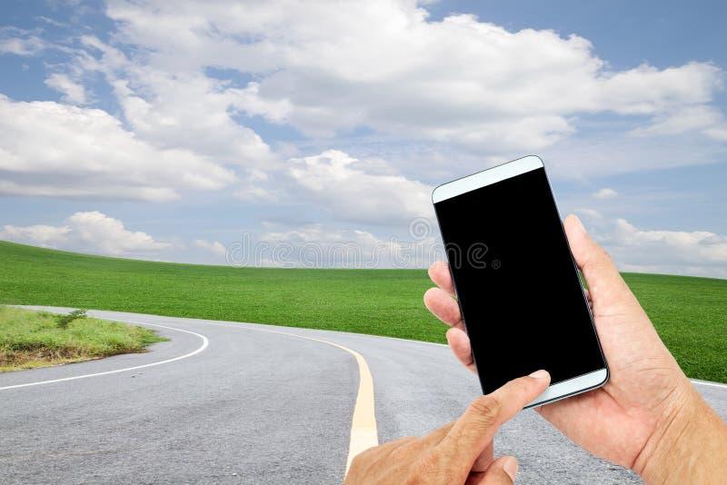Hand die mobiele slimme telefooncontrole op de achtergrond van de wegkromme gebruiken royalty-vrije stock foto's