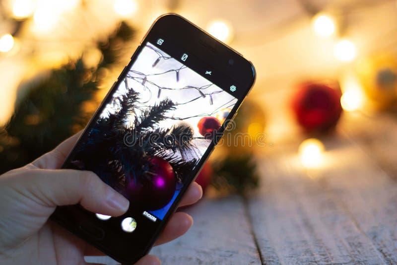 Hand die mobiele smartphone houden die foto van Kerstmisachtergrond nemen met bokeh lichte achtergrond royalty-vrije stock foto