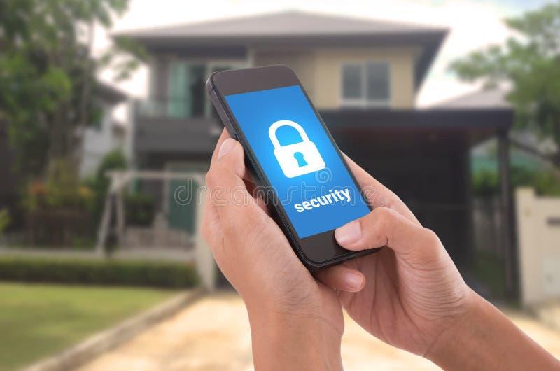 Hand die mobiele telefoon met het huisveiligheid van de conceptentechnologie houden stock afbeeldingen