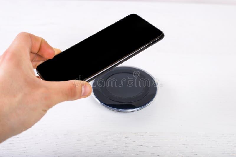 Hand die mobiele telefoon op draadloze lader, modern materiaal op witte achtergrond zet royalty-vrije stock afbeelding