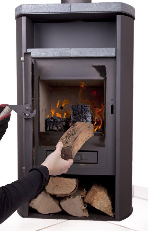 Hand, die modernen hölzernen brennenden Ofen abfeuert stockfotos