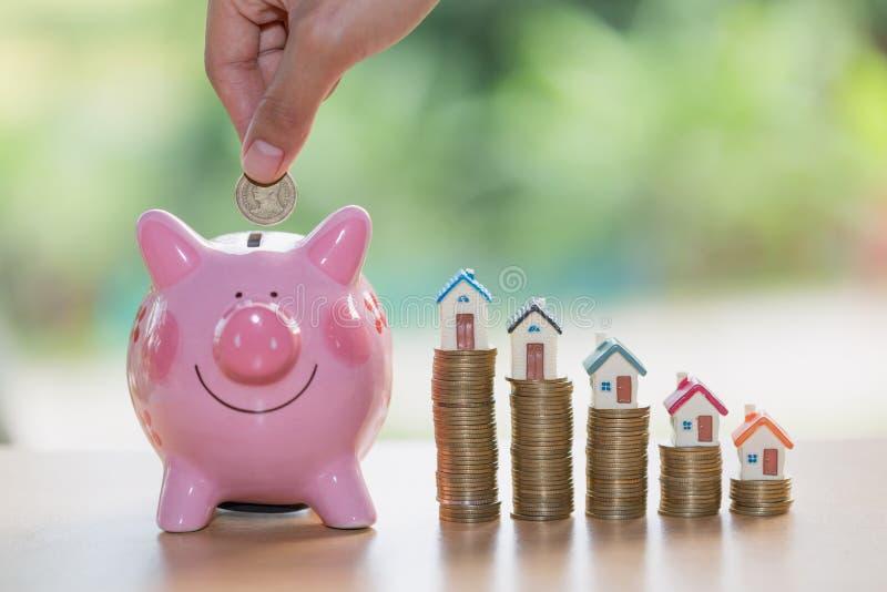 Hand die muntstuk zetten in spaarvarken, die geld besparen om een huis te kopen, stock fotografie