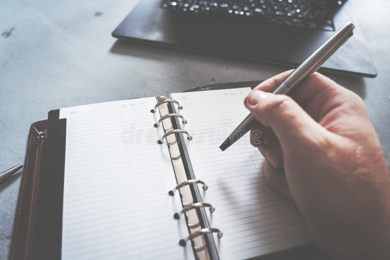 Hand die in notitieboekje met laptop als achtergrond schrijven stock foto's