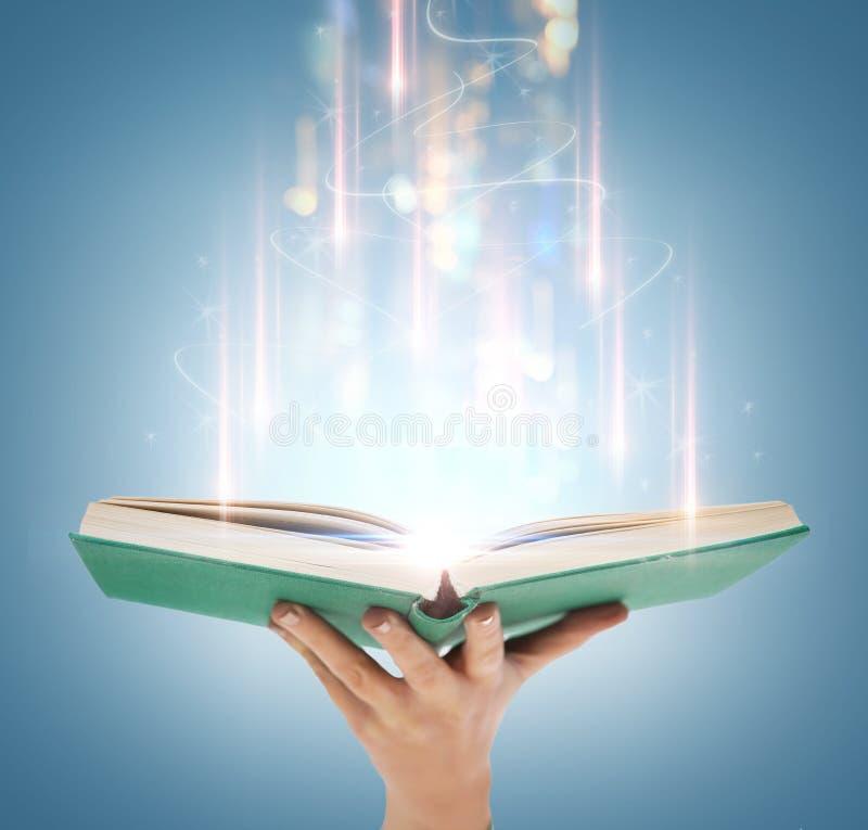 Hand, die offenes Buch mit magischen Lichtern hält lizenzfreie stockbilder