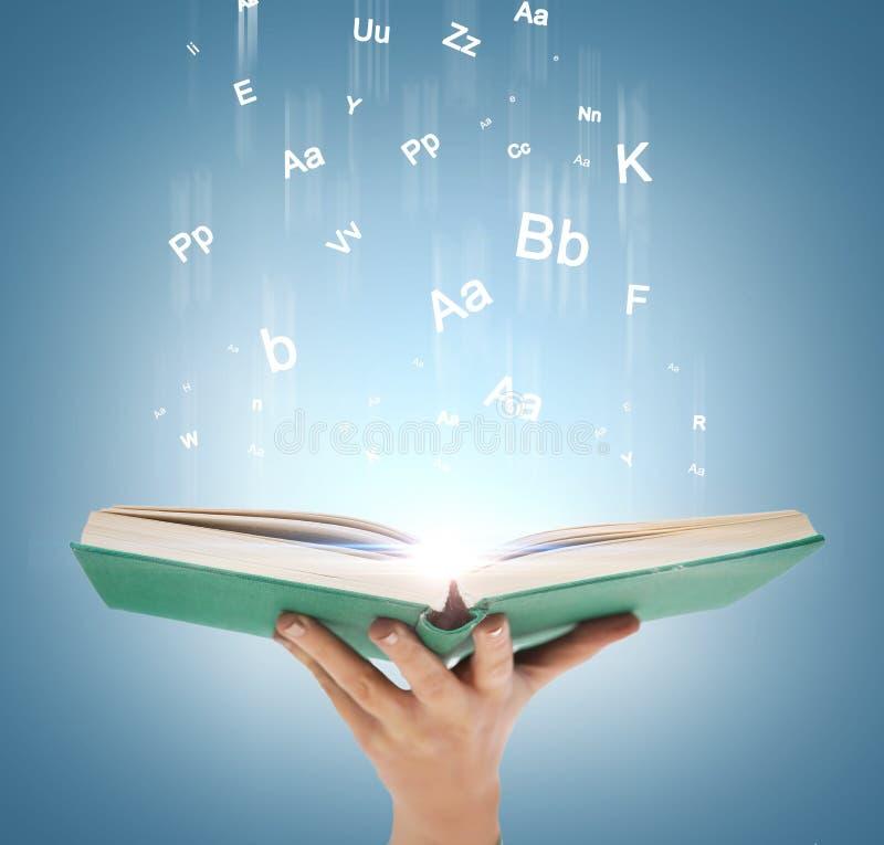 Hand, die offenes Buch mit magischen Lichtern hält lizenzfreies stockbild