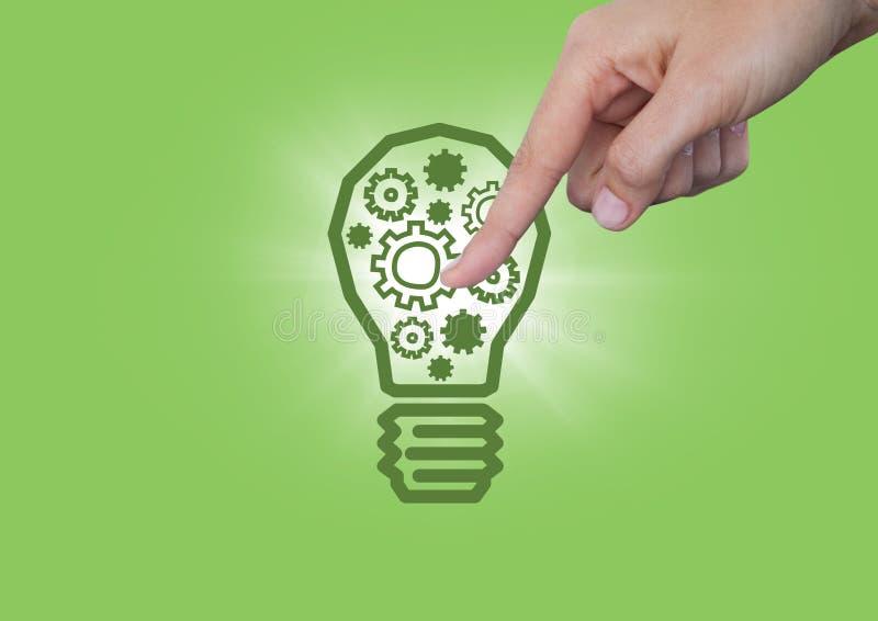 Hand die op radertjes in lightbulb grafisch en gloed richten tegen groene achtergrond royalty-vrije stock foto's
