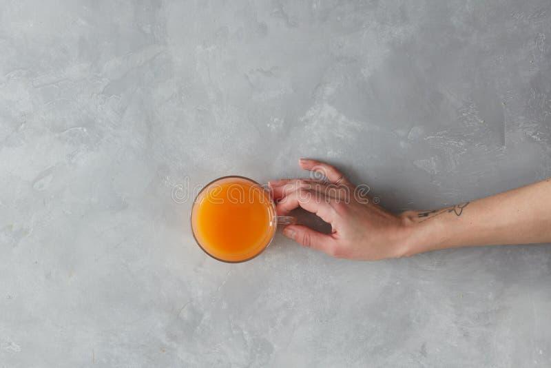 Hand, die Orangensaft hält stockbilder