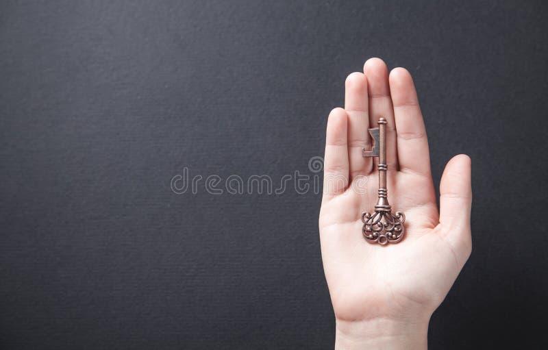 Hand die oude sleutel houden Zaken, succes stock fotografie