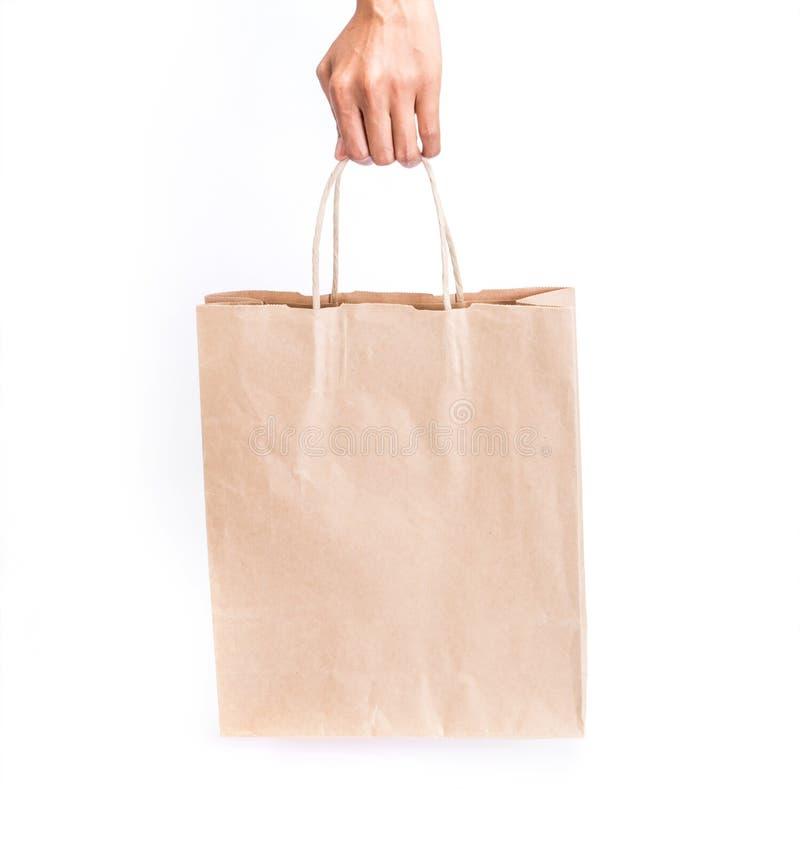 Hand die pakpapier het winkelen zak op witte achtergrond houden stock afbeelding