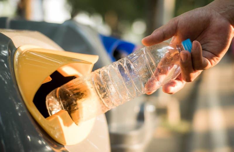 Hand, die Plastikflasche im Wiederverwertungsbehälter, globale Erwärmung wirft stockfotografie