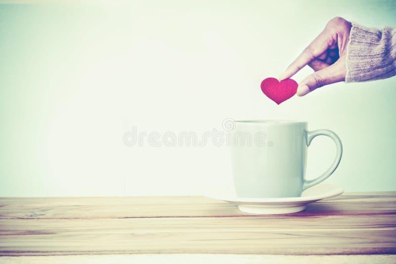 hand die rode hartvorm houden in een mok van de Koffiekop op woode gezet stock afbeelding