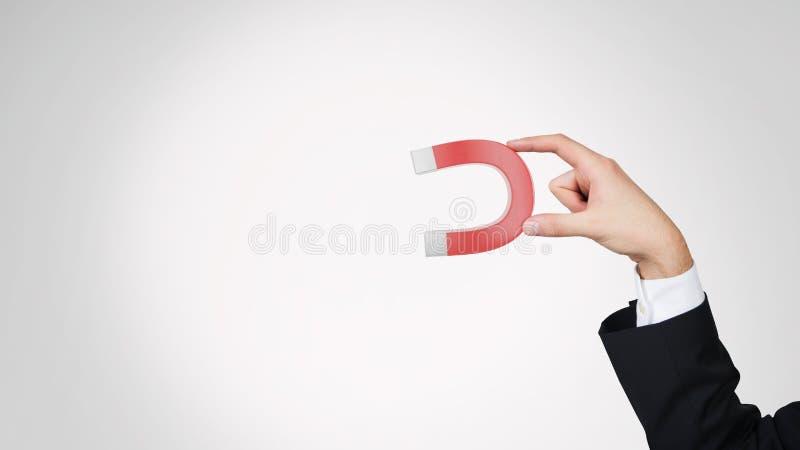 Hand die rode magneet houden stock afbeelding