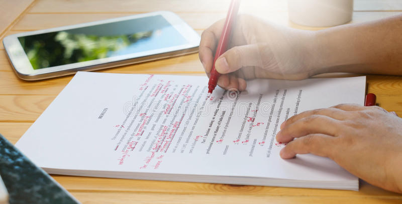 Hand die rode pen over het corrigeren tekst houden stock foto's