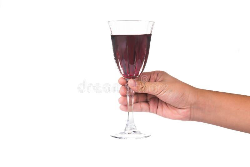 Hand die rode wijn in kristalglas klaar houden te roosteren stock foto's