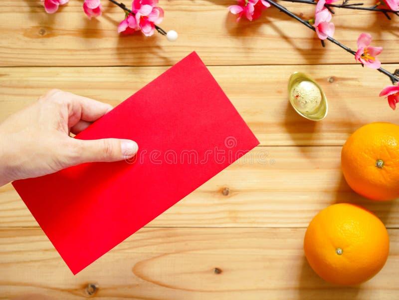 Hand die rood pakket over Chinese Nieuwjaardecoratie geven stock foto