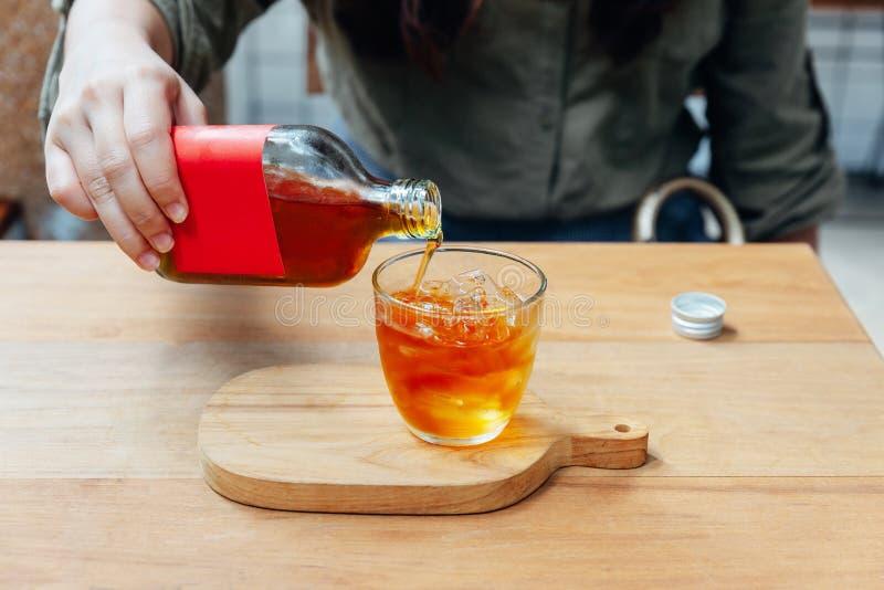 Hand, die roter Aufkleber kalten Gebräu-Tee im Trinkglas mit Eis auf Holztisch gießt lizenzfreie stockfotos