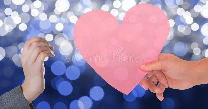 Hand die roze hartvorm geven aan vrouw tegen bokeh stock foto's