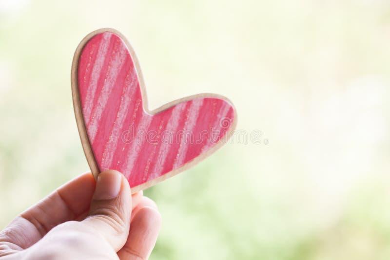 Hand die roze houten hart houden royalty-vrije stock fotografie