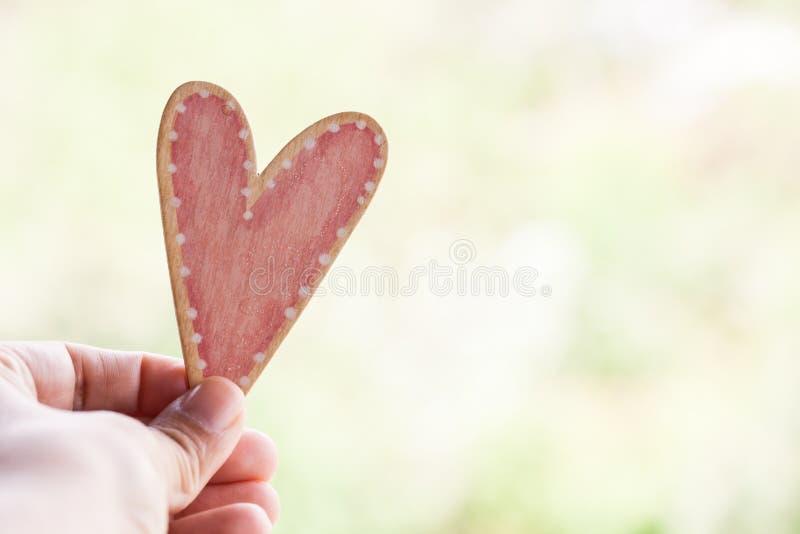 Hand die roze houten hart houden royalty-vrije stock afbeeldingen