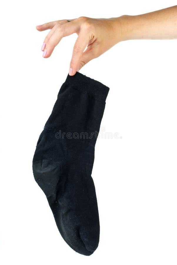 Hand, die schmutzige schwarze Socke anhält stockfoto
