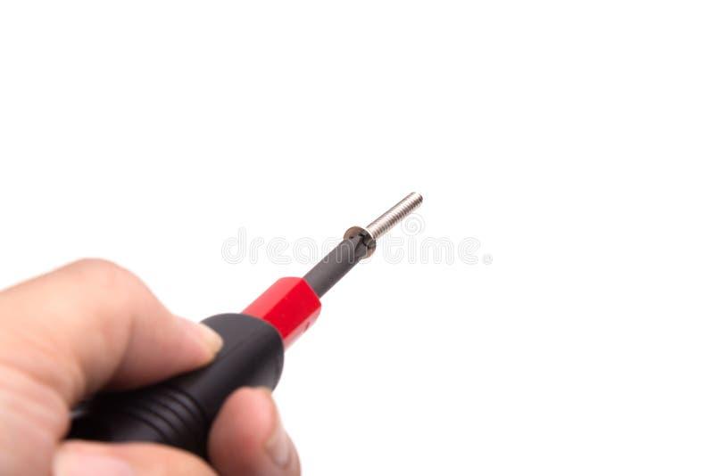 Hand, die Schraubenzieher halten und eine Nuss lokalisiert lizenzfreie stockbilder
