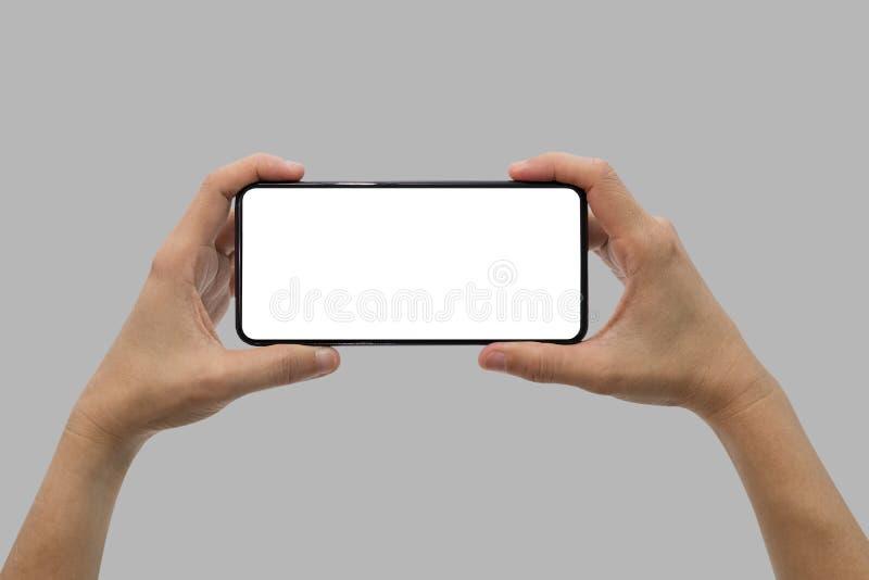 Hand, die schwarzen Handy mit dem leeren Bildschirm lokalisiert auf Grau hält stockfoto