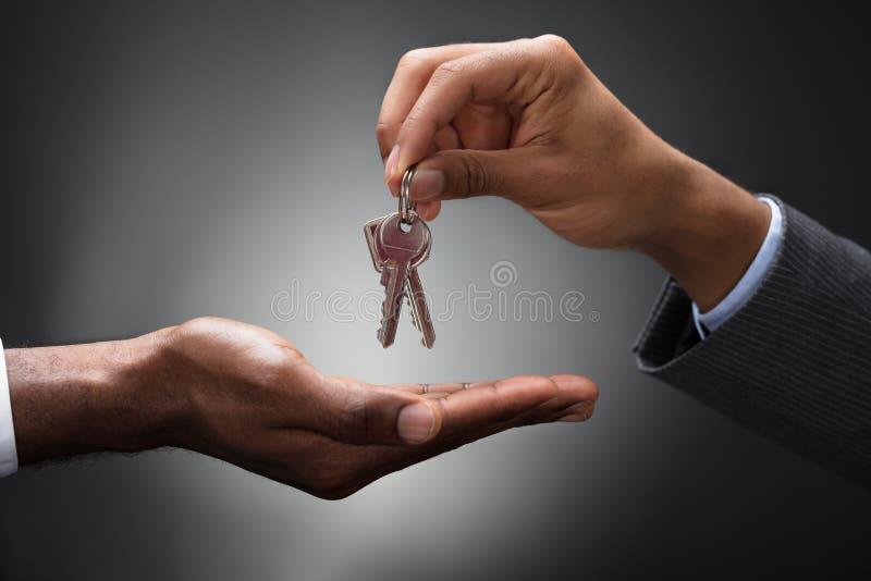 Hand die Sleutels overgaan tot Nieuwe Eigenaar stock afbeelding