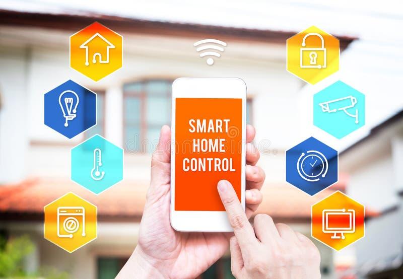 Hand die slimme telefoon met de toepassing van de huiscontrole met onduidelijk beeld houden stock afbeeldingen