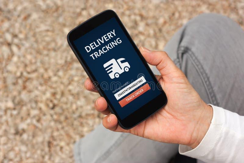Hand die slimme telefoon met levering het volgen concept op puinkegel houden royalty-vrije stock fotografie