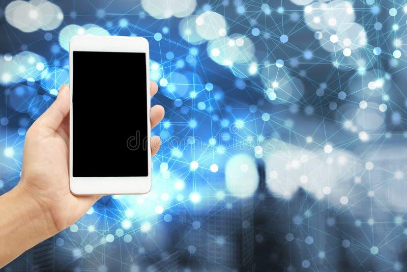 hand die slimme telefoon over moderne abstracte netwerk en stadsachtergrond houden stock afbeeldingen