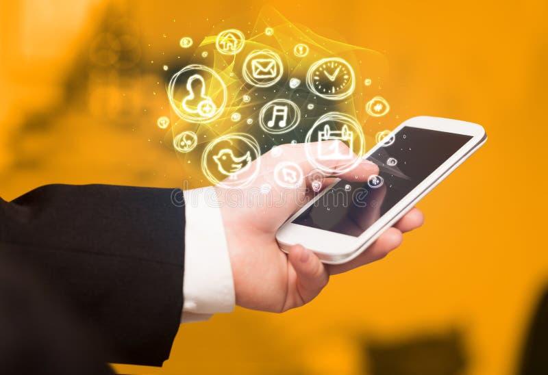 Hand, die Smartphone mit beweglichen APP-Wahlen hält stockbilder
