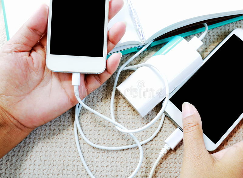 Hand, die Smartphone mit laufendem und Aufladungsteig hält lizenzfreie stockfotos